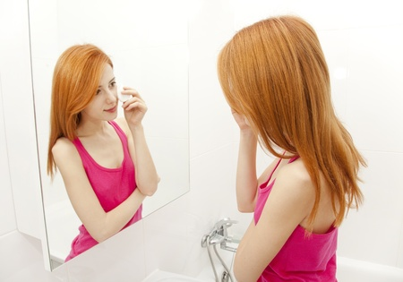 Beautiful redhead young woman with fresh skin of face in bathroom photo