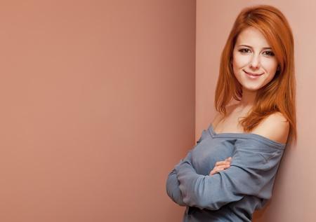 Beautiful redhead girl near wall. Stock Photo - 11670923