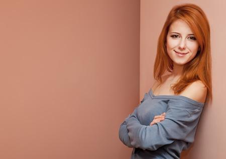 Beautiful redhead girl near wall. Stock Photo - 11670923