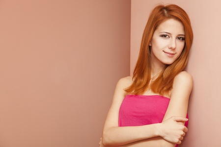 Beautiful redhead girl near wall. Stock Photo - 11670942
