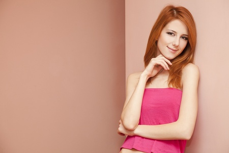 Beautiful redhead girl near wall. Stock Photo - 11670941