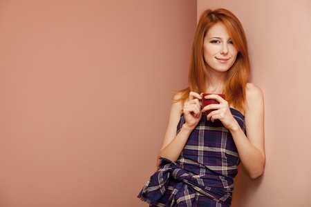 Beautiful redhead girl near wall with cup of coffee. Stock Photo - 11670943