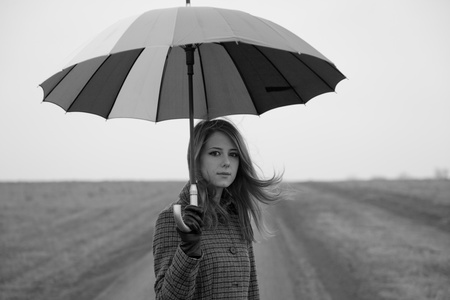 enchantress: Lonely girl with umbrella at country road. Photo in old black and white style with little noise. Stock Photo