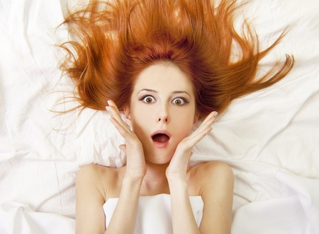 luxuriate: Surprised red-haired girl in bed. Studio shot.
