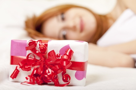 Red-haired girl in bed with gift. Studio shot. photo