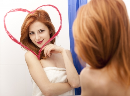 Redhead girl near mirror with heart at it in bathroom. Stock Photo