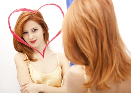 Redhead girl near mirror with heart at it in bathroom. Stock Photo - 11851450