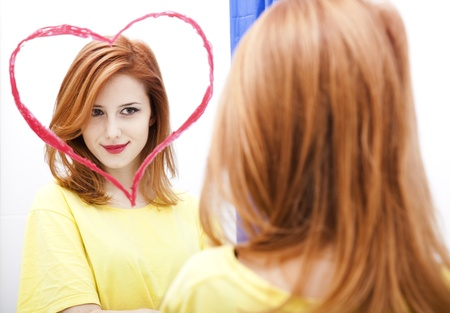 Redhead girl near mirror with heart at it in bathroom. Stock Photo - 11851428