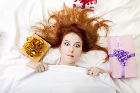 luxuriate: Surprised red-haired girl in bed with gifts. Studio shot. Stock Photo