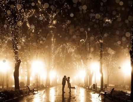 Coppia camminare al vicolo in luci notturne. Foto in stile vintage multicolore.