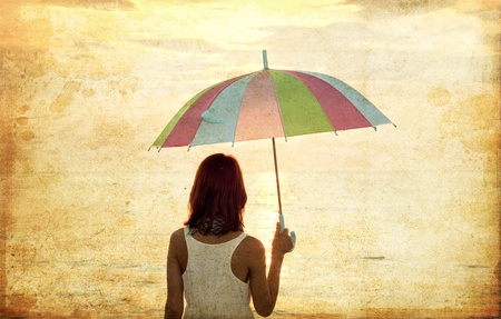 Girl with umbrella at sea coast. Photo in old image style. photo