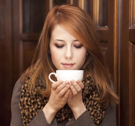 tomando café: Estilo chica pelirroja consumo de café cerca de las puertas de madera. Foto de archivo