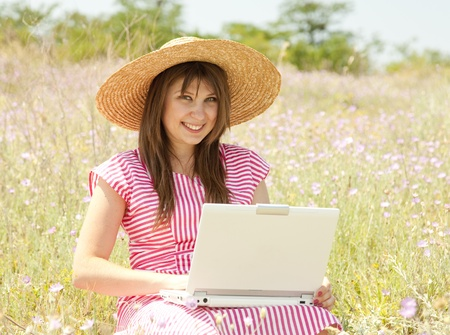 Beautiful brunette girl in hat at the park with computer. photo