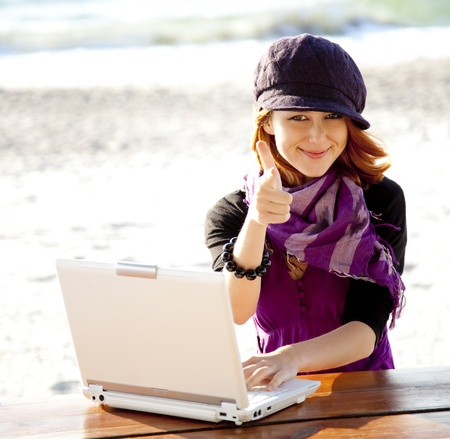 Portrait of red-haired girl with laptop at beach. Stock Photo - 11851419