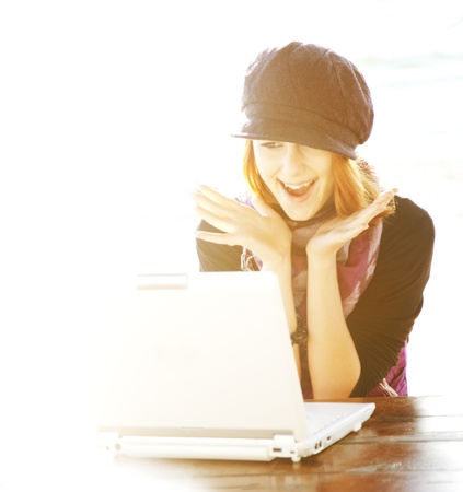 Portrait of red-haired girl with laptop and backside light. photo