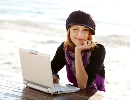 Portrait of red-haired girl with laptop at beach. photo