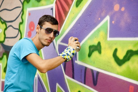 to hasten: Graffiti painter drawing a picture on the wall
