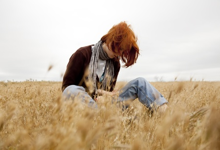 Lonely sad red-haired girl at field photo