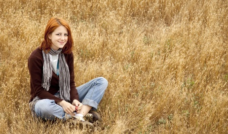 Beautiful red-haired girl sitting at yellow autumn grass. Stock Photo - 11851270