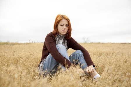 sad teen: Lonely sad red-haired girl at field