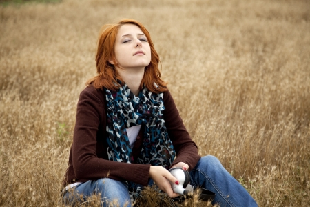 sad lonely girl: Lonely sad red-haired girl at field