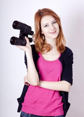 shyness: Teen redhead girl with binoculars Stock Photo