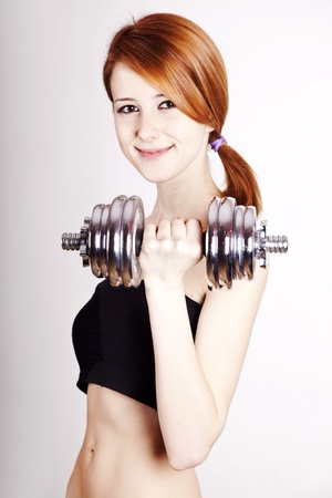 Attractive teenage girl working-out with dumbbell Stock Photo