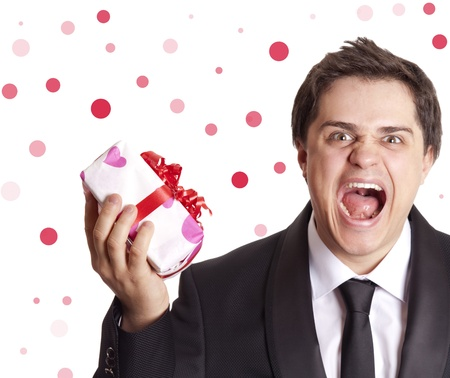 suitor: A angry man holding present box in formal black tux with tie isolated on white background Stock Photo