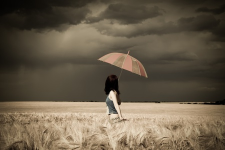 Girl with umbrella at field in retro style Stock Photo