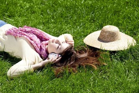 Brunette girl with headphone lies in the park. photo