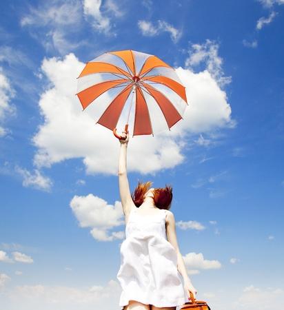 enchantress: Redhead enchantress with umbrella and suitcase at spring