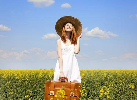 enchantress: Redhead enchantress with suitcase at spring rapeseed field.