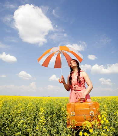 Brunette enchantress with umbrella and suitcase at spring rapeseed field. photo