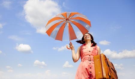 the enchantress: Brunette enchantress with umbrella and suitcase  Stock Photo