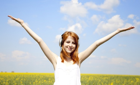 Redhead girl with headphone at field. photo