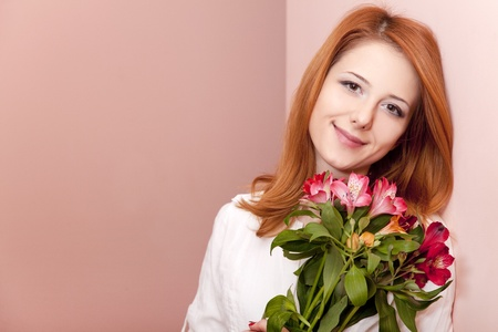 Redhead girl with flowers indoor. Stock Photo - 12324028
