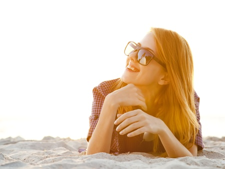 Red-head girl with headphones at the beach in sunrise. photo