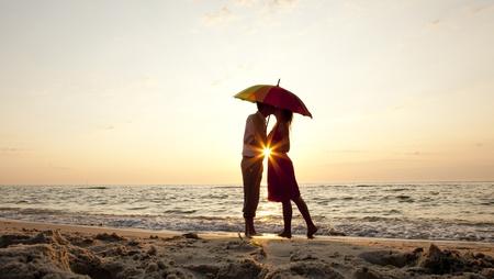 pareja besandose: Pareja bes�ndose bajo el paraguas en la playa en el atardecer.