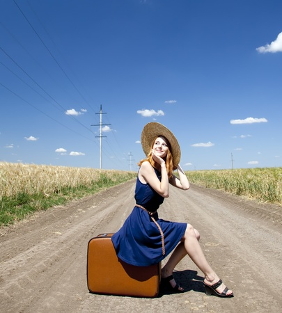 Lonely girl with suitcase at country road. photo
