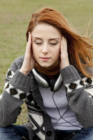 Sad girl with headphones sitting at green spring grass. Stock Photo - 13214529
