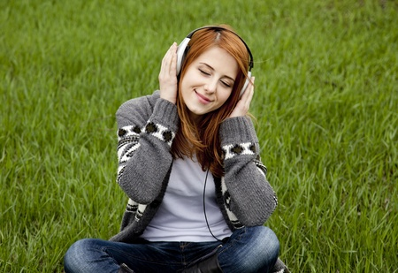 Young fashion girl with headphones sitting at green spring grass. photo