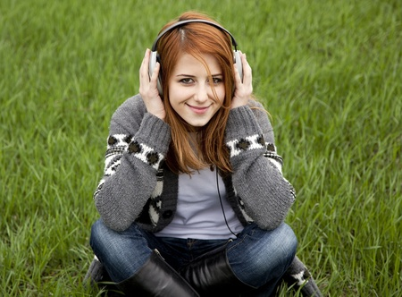 earphone: Young fashion girl with headphones sitting at green spring grass.