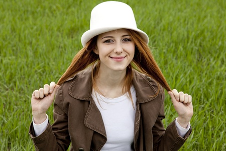 Young fashion girl in white hat at green spring grass. photo