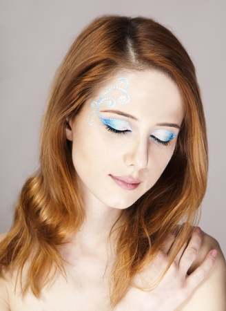 Portrait of beautiful redhead girl with style make-up. photo