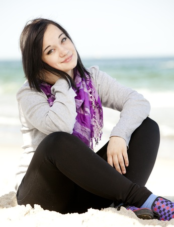 Funny teen girl sitting on the sand at the beach. Stock Photo - 13418377