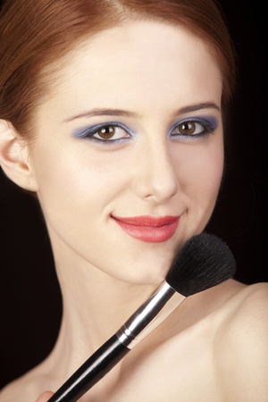 makeup brush: Portrait of beautiful redhead girl with style make-up and brush.