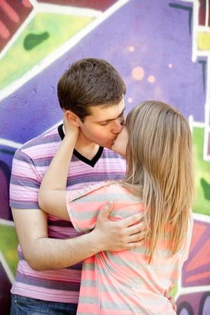 Young couple kissing near graffiti background.