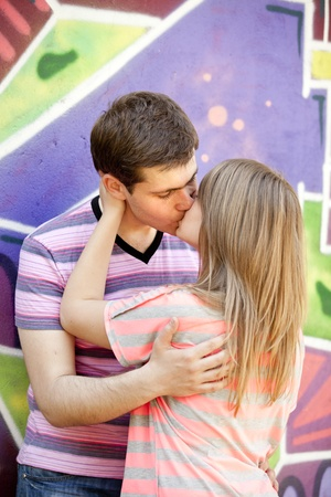 lovers kissing: Young couple kissing near graffiti background.