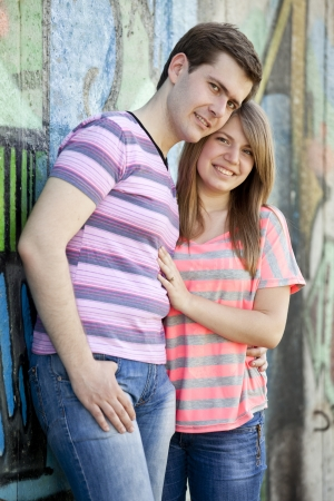 Young couple near graffiti background. photo