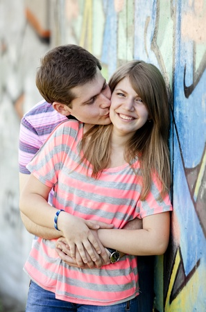 young couple kissing: Young couple kissing near graffiti background.